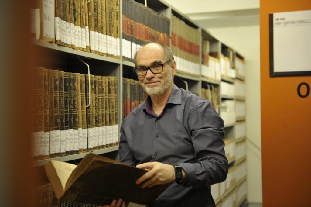 En mann med blå skjorte og briller står og holder en protokoll mellom arkivreoler.