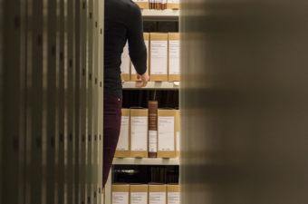 Vi ser ryggen av en kvinne mellom reolene i et arkivmagasin