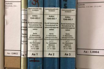 Bildet viser en reol i arkivmagasinet med mange bokser med etiketter på